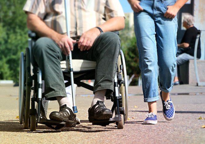 man-in-wheelchair-girl-walking-beside