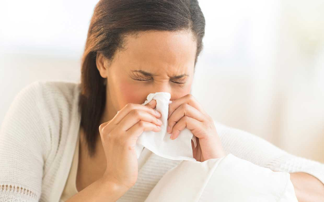 Woman blowing her nose using kleenex